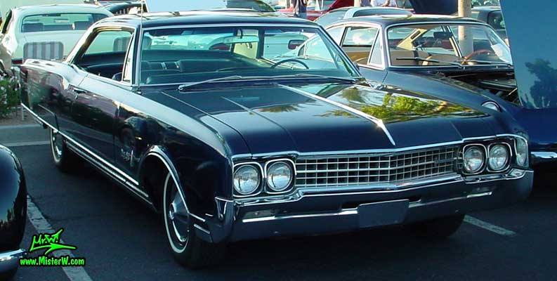 Photo of a dark blue 1966 Oldsmobile Ninety Eight 2 Door Hardtop Coupe at the Scottsdale Pavilions Classic Car Show in Arizona. 1966 Oldsmobile Ninety Eight Coupe Frontview