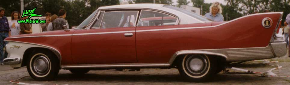 Photo of a dark red 1960 Chrysler Plymouth Fury 2 Door Hardtop Coupe at a classic car meeting in Germany. Sideview of a 1960 Plymouth Fury Coupe