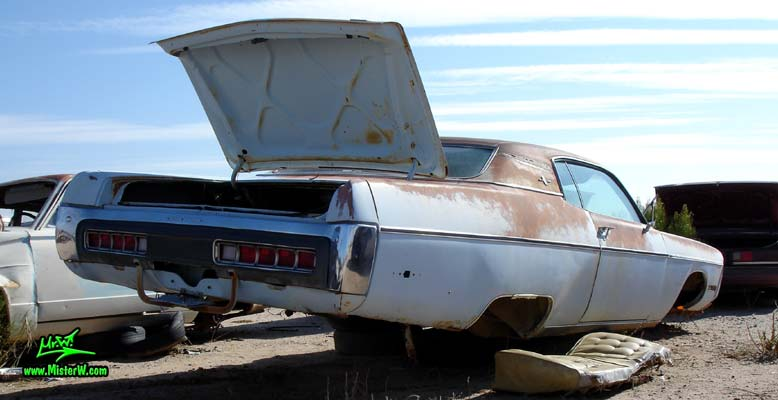 Photo of a white & rusty 1972 Chrysler Plymouth 2 door hardtop coupe at a junk yard in Phoenix, Arizona. Rearview of a 72 Plymouth Fury