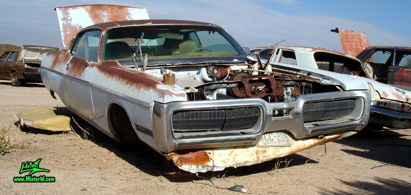Photo of a white & rusty 1972 Chrysler Plymouth 2 door hardtop coupe at a junk yard in Phoenix, Arizona. Frontview of a 72 Plymouth Fury