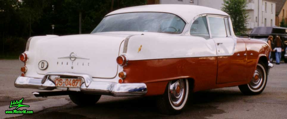 Photo of a red & white 1955 Pontiac 2 Door Hardtop Coupe at a Classic Car Meeting in Germany. Tailfins of a 55 Pontiac Coupe