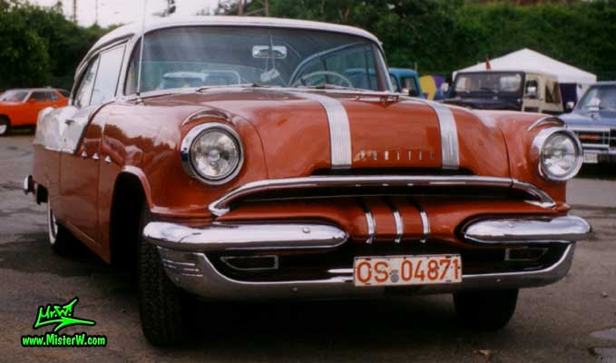 Photo of a red & white 1955 Pontiac 2 Door Hardtop Coupe at a Classic Car Meeting in Germany. Frontview of a 55 Pontiac