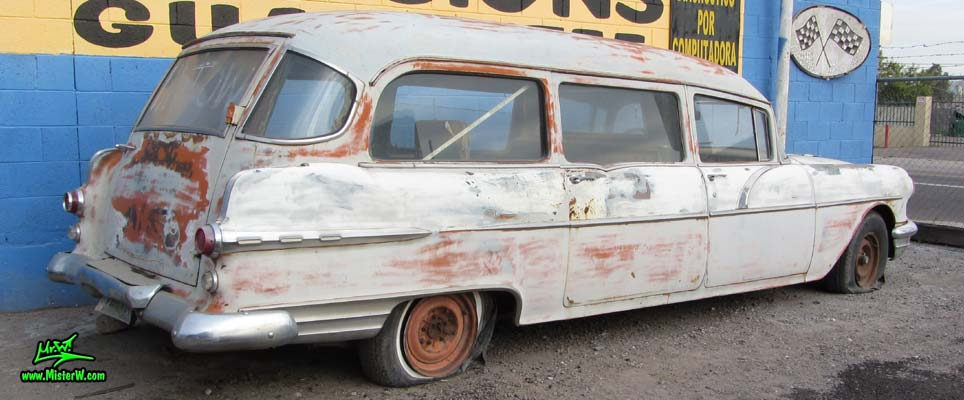 Photo of a grey primered 1956 Pontiac ambulance in Phoenix, Arizona. Tail fins of a 56 Pontiac Ambulance Wagon
