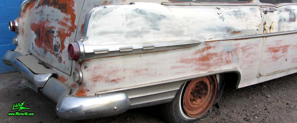 Photo of a grey primered 1956 Pontiac ambulance in Phoenix, Arizona. Tailfin & chrome trim of a 56 Pontiac Ambulance Wagon