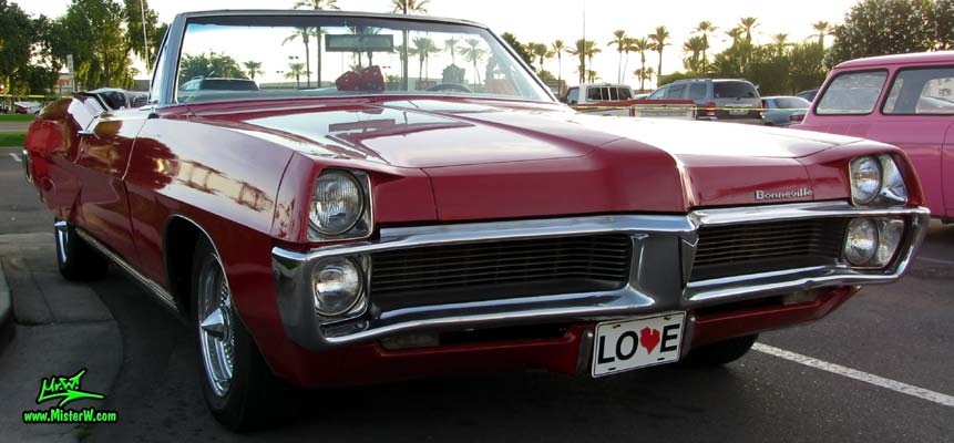 Photo of a red 1967 Pontiac Bonneville Convertible at the Scottsdale Pavilions Classic Car Show in Arizona. 67 Pontiac Agressive Front Grill
