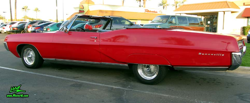Photo of a red 1967 Pontiac Bonneville Convertible at the Scottsdale Pavilions Classic Car Show in Arizona. Side of a 67 Pontiac Bonneville Convertible