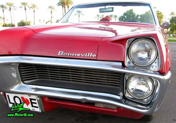 Photo of a red 1967 Pontiac Bonneville Convertible at the Scottsdale Pavilions Classic Car Show in Arizona. Head Lights of a 67 Pontiac Convertible