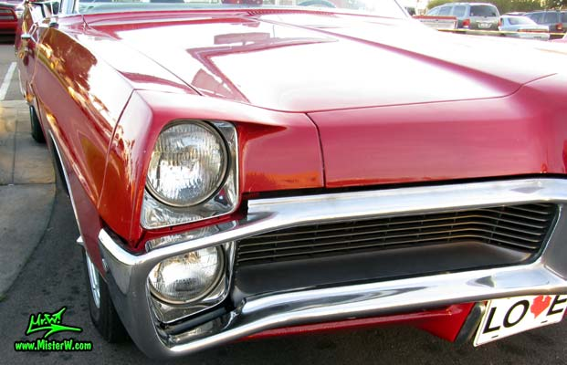 Photo of a red 1967 Pontiac Bonneville Convertible at the Scottsdale Pavilions Classic Car Show in Arizona. Front Grill & Bumper of a 67 Pontiac Bonneville Convertible