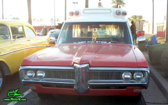 Photo of a red & white 1968 Pontiac Bonneville Ambulance at the Scottsdale Pavilions Classic Car Show in Arizona. Frontview of a 68 Pontiac Bonneville Ambulance
