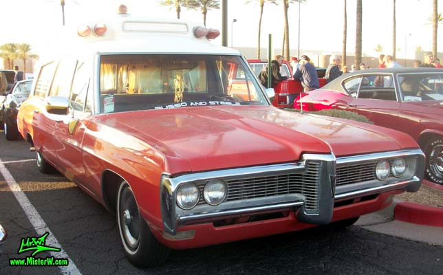Photo of a red & white 1968 Pontiac Bonneville Ambulance at the Scottsdale Pavilions Classic Car Show in Arizona. Sideview of a 68 Pontiac Bonneville Ambulance