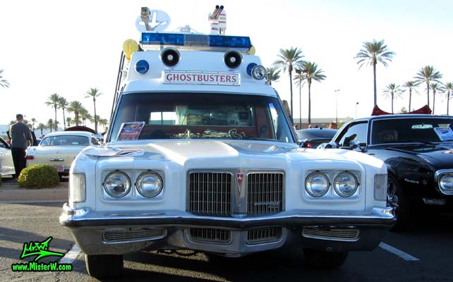 Photo of a red & white Pontiac Bonneville Ambulance at the Scottsdale Pavilions Classic Car Show in Arizona. Frontview of a 72 Pontiac Pontiac Bonneville Ambulance