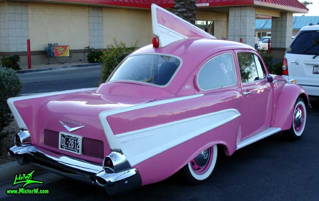 Photo of a customized pink Volkswagen Kaefer / Bug / Beetle modified with 1957 Chevrolet Fins at the Scottsdale Pavilions Classic Car Show in Arizona. VW Käfer customized with 1957 Chevrolet Fins