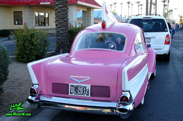 Photo of a customized pink Volkswagen Kaefer / Bug / Beetle modified with 1957 Chevrolet Fins at the Scottsdale Pavilions Classic Car Show in Arizona. The back of the VolksChevrolet a Volkswagen Kaefer morphed with a 1957 Chevrolet